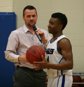 SCA Athletic Director and Varsity Boys Basketball Coach Jake Kates presents the game ball to SCA Senior Taurin Hughes.