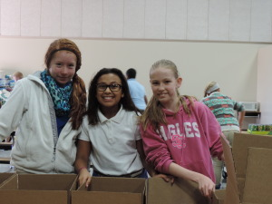 SCA 6th graders Tennisen, Addy Valladaras, and Grace Kennedy help assemble boxes of food.