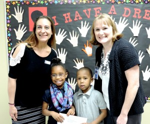Paradise Parks Representative Carolyn Rodriguez presents the grand prize of Max Paks for a family of four to SCA 1st grader Leah Yancey and her brother Aiden, with Elementary Vice Principal Mrs. Charissa Sanders.