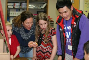 SCA junior Zach Wu enjoys sharing his Chinese Culture with SCA first grade student Cooper Whitfield and his Mom Elaine, and SCA third grader Avery Whitfield as they open a traditional fortune cookie.