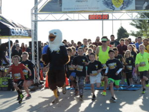 """The SCA mascot """"Screech"""" leads the way as the Eagle Egg 5K begins in front of Frontier Justice."""