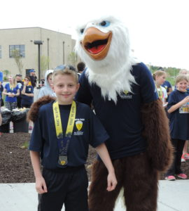 """SCA's """"Screech"""" with SCA third Grader Nicolas Cipolla, who placed first in the 8-9 year old male category with a time of 23:33."""